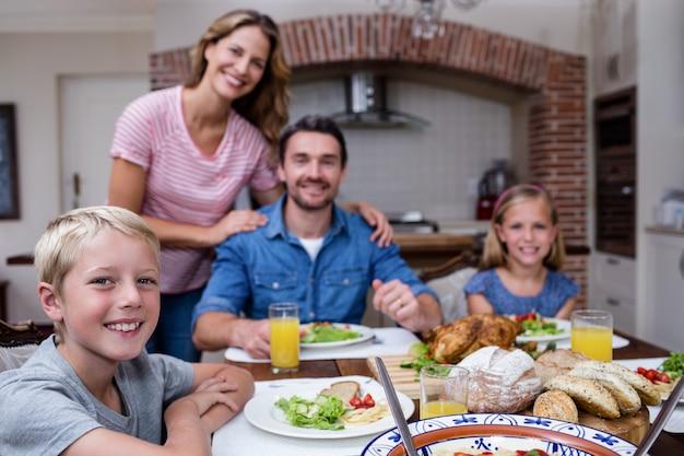 Portret szczęśliwa rodzina ma posiłek w kuchni Premium Zdjęcia