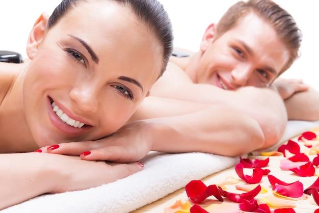 Portret Szczęśliwa Uśmiechnięta Para Relaks W Salonie Spa Z Gorącymi Kamieniami Na Ciele. Darmowe Zdjęcia