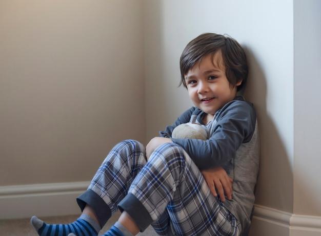 Portret Szczęśliwego Dzieciaka Z Uśmiechniętą Twarzą Relaksującą Się W Domu, Zdrowe Dziecko Chłopca Siedzącego Na Dywanie, Grającego Z Misiem I Patrząc Na Kamery, Dystans Społeczny Duromg Covid Blokada W Dół Premium Zdjęcia