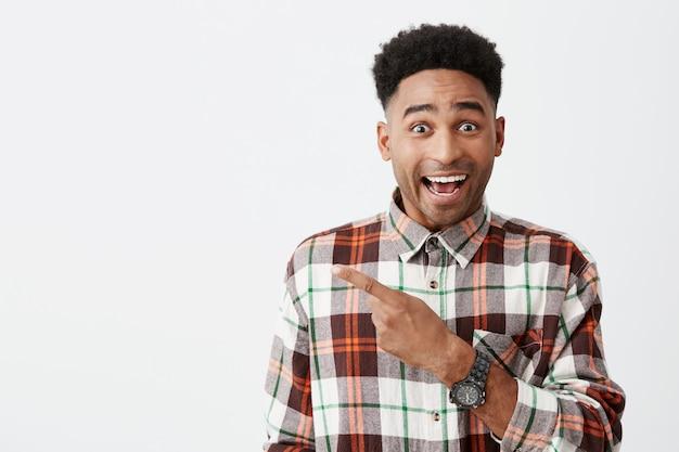 Portret Szczęśliwego Młodego, Dobrze Wyglądającego, Podpalanego Studenta Z Fryzurą Afro W Uśmiechniętej Swobodnej Kraciastej Koszuli, Wskazując Palcem Podekscytowaną Twarz Darmowe Zdjęcia