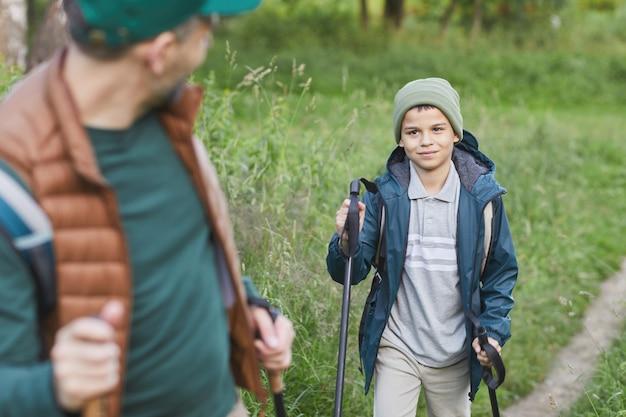 Portret Szczęśliwego Ojca I Syna Wędrujących Razem I Idących Pod Górę, Skup Się Na Uśmiechniętym Chłopcu Z Kijkami, Skopiuj Przestrzeń Premium Zdjęcia