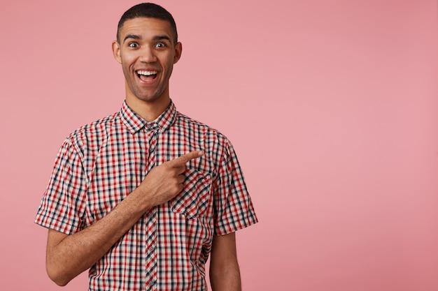 Portret Szczęśliwego Zdumionego Młodego Atrakcyjnego Ciemnoskórego Faceta W Kraciastej Koszuli, Szeroko Otwartych Ustach I Oczach, Stoi Na Różowym Tle, Chce Zwrócić Twoją Uwagę Na Miejsce Po Prawej Stronie. Darmowe Zdjęcia