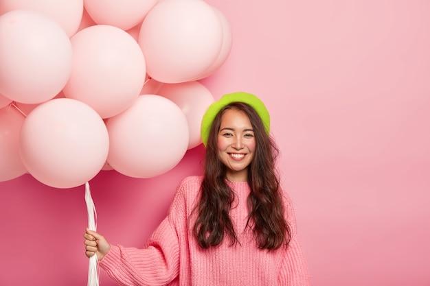 Portret Szczęśliwej Azjatyckiej Brunetki Uśmiecha Się Delikatnie, Przychodzi Na Wieczór Panieński, Trzyma Wielki Bukiet Balonów, Nosi Zielony Beret I Za Duży Sweter. Darmowe Zdjęcia