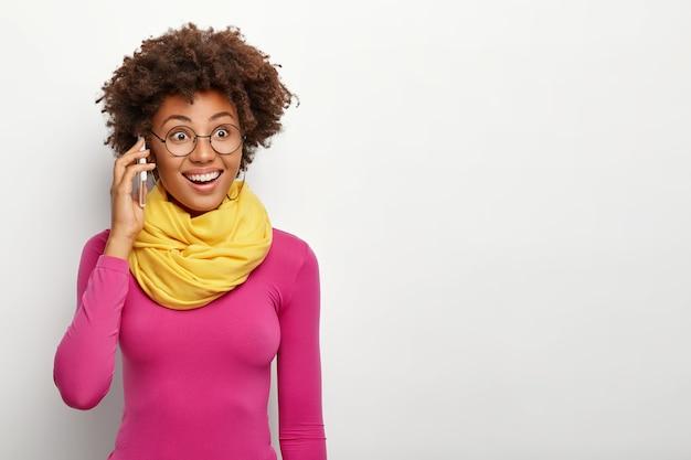 Portret Szczęśliwej Ciemnoskórej Kobiety Z Fryzurą Afro, Nosi Okulary, Poloneck I żółty Szalik Na Szyi, Ma Radosny Wyraz Twarzy, Modele Na Białej ścianie Studia Darmowe Zdjęcia