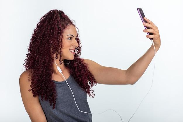 Portret Szczęśliwej Kobiety Za Pomocą Telefonu Komórkowego I Słuchawek, Uśmiechając Się I Robiąc Selfie Premium Zdjęcia