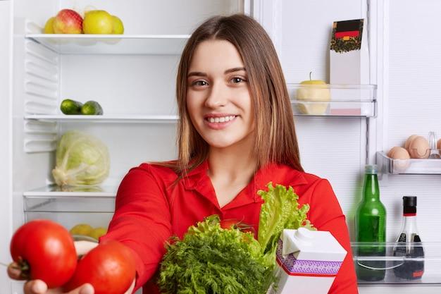 Portret Szczęśliwej Uroczej Kobiety O Wesołym Wyrazie, Ubrany W Czerwoną Bluzkę, Trzyma świeże Warzywa, Demonstruje Czerwone Pomidory, Z Radością Rozpocząć Nowy Dzień, Robi Dla Siebie Sałatkę Wegetariańską Premium Zdjęcia