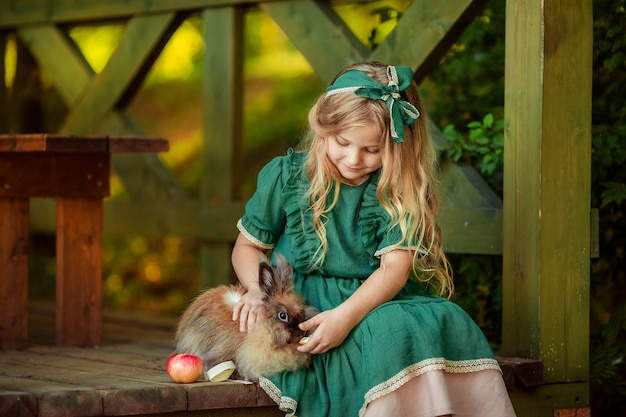 Portret Szczęśliwy Dzieciństwo Z Cute Girl O Blond Włosach W Zielonej Sukience, Która Karmi Czerwone Jabłko Królika. Siedzą Na Schodach Drewnianej Altany. Premium Zdjęcia