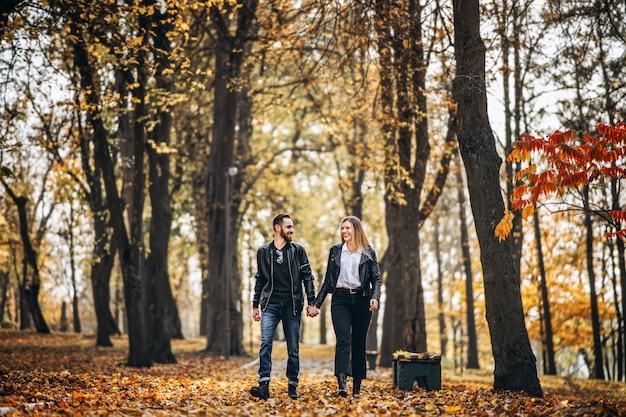 Portret Szczęśliwy Kochający Pary Chodzić Plenerowy W Jesień Parku. Mężczyzna I Kobieta, Trzymając Się Za Ręce I Smilling Premium Zdjęcia