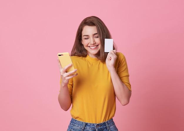 Portret Szczęśliwy Młodej Kobiety Mienia Telefon Komórkowy I Kredytowa Karta Odizolowywający Nad Menchiami. Premium Zdjęcia
