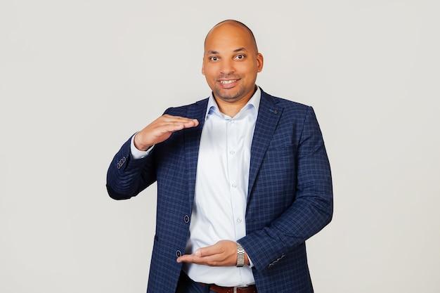 Portret Szczęśliwy Młody Afroamerykanin Biznesmen Facet Gestykuluje Rękami Pokazując Duży I Duży Rozmiar Znak, Symbol Miary. Premium Zdjęcia