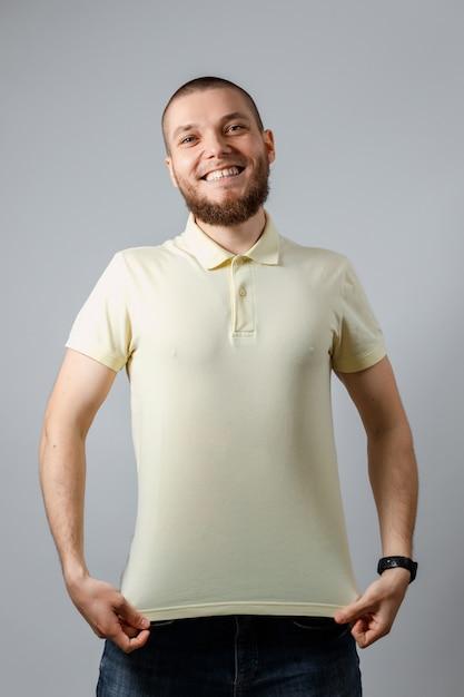 Portret Szczęśliwy Młody Człowiek W żółtej Koszulce Mocap Na Szaro. Premium Zdjęcia