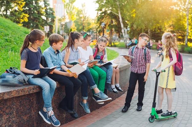 Portret szczęśliwy szkolnych kolegów. koledzy siedzą z książkami w drewnianej ławce w parku miejskim i studiują w słoneczny dzień. Premium Zdjęcia