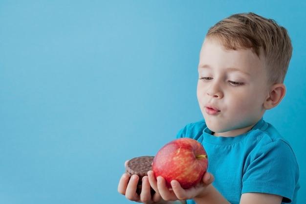 Portret Szczęśliwy, Uśmiechnięty Chłopiec Wybierając Fast Foodów. Zdrowe A Niezdrowe Jedzenie. Zdrowe A Niezdrowe Jedzenie, Nastolatek Wybiera Ciastko Lub Jabłko Premium Zdjęcia