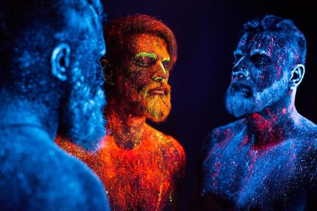 Portret Trzech Brodatych Mężczyzn Pomalowanych We Fluorescencyjne Proszki. Premium Zdjęcia