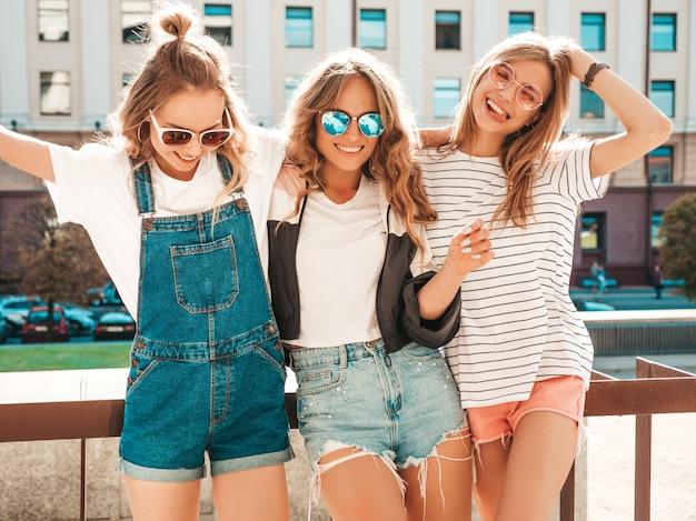 Portret Trzech Młodych Pięknych Uśmiechniętych Hipster Dziewcząt W Modne Letnie Ubrania. Seksowne Beztroskie Kobiety Pozowanie Na Ulicy. Pozytywne Modele Zabawy W Okularach Przeciwsłonecznych. Przytulanie Darmowe Zdjęcia