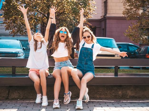 Portret Trzech Młodych Pięknych, Uśmiechniętych Hipster Dziewcząt W Modne Letnie Ubrania. Seksowne Beztroskie Kobiety Siedzą Na ławce Na Ulicy. Pozytywne Modele Zabawy W Okularach Przeciwsłonecznych. Podnoszenie Rąk Darmowe Zdjęcia