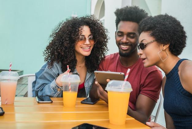 Portret Trzech Przyjaciół Afro, Wspólnej Zabawy I Korzystania Z Cyfrowego Tabletu Na świeżym Powietrzu W Kafeterii. Koncepcja Technologii. Premium Zdjęcia