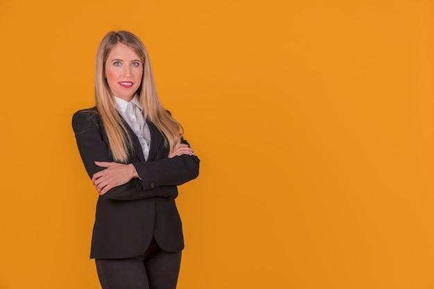Portret ufna młoda kobieta z jej ręką krzyżował pozycję przeciw pomarańczowemu tłu Darmowe Zdjęcia