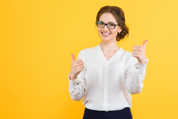 Portret Ufna Piękna Młoda Uśmiechnięta Szczęśliwa Biznesowa Kobieta Z Aprobatami Na Kolor żółty ścianie Premium Zdjęcia