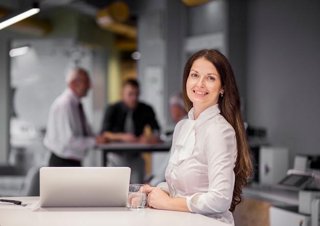 Portret ufny bizneswoman z laptopem i szkłem woda przy miejscem pracy Darmowe Zdjęcia