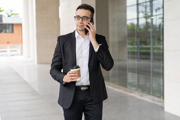 Portret ufny młody biznesmen opowiada na telefonie komórkowym Darmowe Zdjęcia