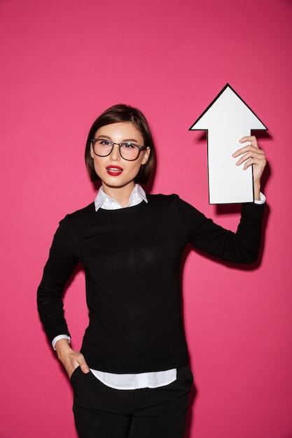 Portret Ufny Młody Bizneswoman Wskazuje Up Z Strzała Darmowe Zdjęcia