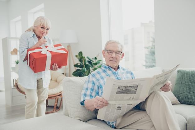 Portret Uroczej Babci Niosącej Wielki Romantyczny Prezent Dla Dziadka W Jasnobiałym Wnętrzu Domu Z Salonem Premium Zdjęcia