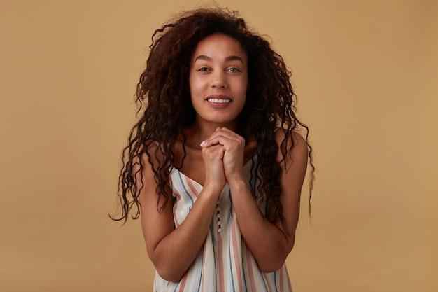 Portret Uroczej Młodej Zadowolonej Długowłosej Kręconej Ciemnoskórej Kobiety Z Naturalnym Makijażem, Z Uniesionymi Rękami I Wyglądającą Pozytywnie, Odizolowana Na Beżu Darmowe Zdjęcia