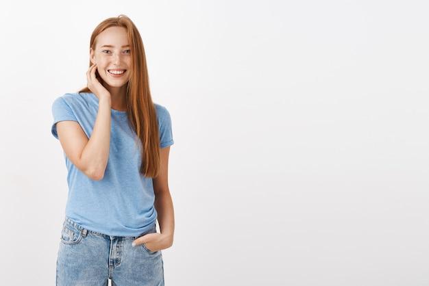 Portret Uroczej Szczęśliwej, Entuzjastycznej Kobiety Z Rudymi Włosami I Piegami, Uśmiechnięta Przyjazna, Dotykająca Szyja I Trzymająca Rękę W Kieszeni, Nieśmiała I Nieśmiała Rozmawiająca Z Uroczym Baristą Podczas Zamawiania Kawy Darmowe Zdjęcia