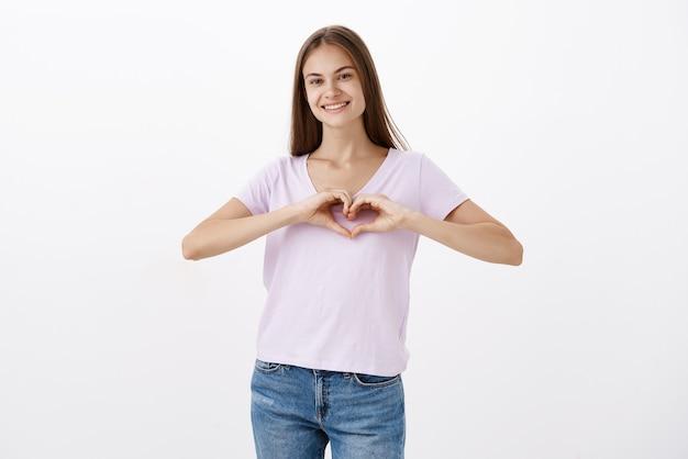 Portret Uroczej, Wesołej Młodej Dziewczyny Rasy Kaukaskiej W Swobodnej Koszulce, Uśmiechającej Się Radośnie, Wyrażającej Miłość, Pokazującej Gest Serca Na Klatce Piersiowej, Wyznającej Ciepłe Uczucia Rodzinie Darmowe Zdjęcia