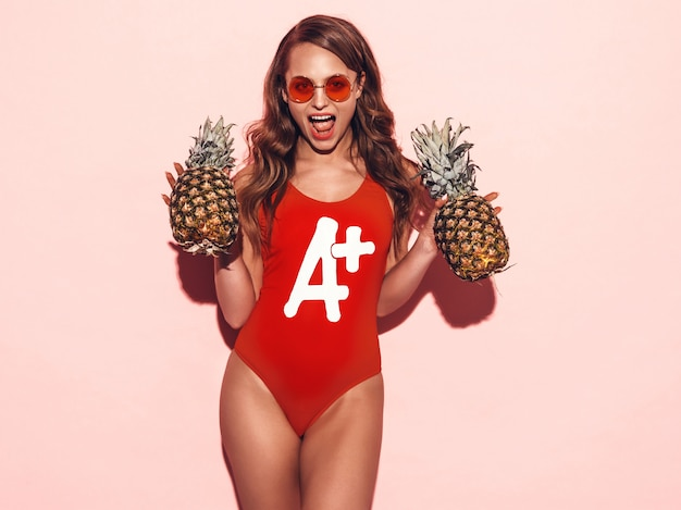 Portret Uśmiechnięta Brunetki Dziewczyna W Lata Czerwonym Stroju Kąpielowym Odzieżowym I Round Okularach Przeciwsłonecznych. Seksowna Kobieta Z świeżymi Ananasami. Pozowanie Modelu Pozytywnego Darmowe Zdjęcia