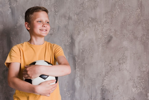 Portret uśmiechnięta chłopiec mienia piłki nożnej piłka przed betonową ścianą Darmowe Zdjęcia