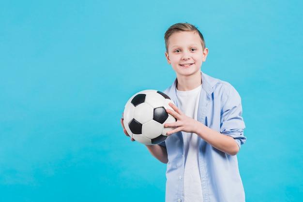 Portret uśmiechnięta chłopiec trzyma piłki nożnej piłkę w ręku stoi przeciw niebieskiemu niebu Darmowe Zdjęcia