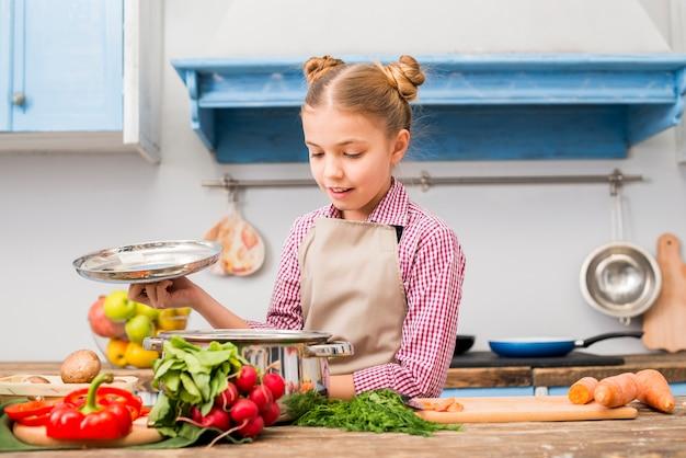 Portret Uśmiechnięta Dziewczyna Patrzeje Stal Nierdzewna Gotuje Garnek W Kuchni Darmowe Zdjęcia