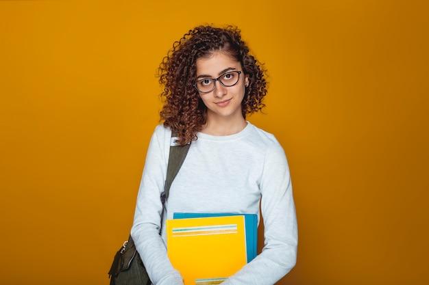 Portret uśmiechnięta indiańska żeńskiego ucznia dziewczyna z książkami w szkłach. Premium Zdjęcia