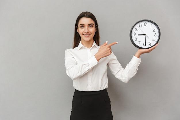 Portret Uśmiechnięta Kobieta Sukcesu W Białej Koszuli I Czarnej Spódnicy, Wskazując Palcem Na Okrągły Zegar, Trzymając W Ręku, Odizolowane Na Szarej ścianie Premium Zdjęcia