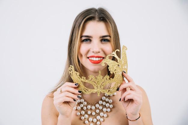 Portret Uśmiechnięta Kobieta Trzyma Złotą Karnawał Maskę W Kolii Darmowe Zdjęcia