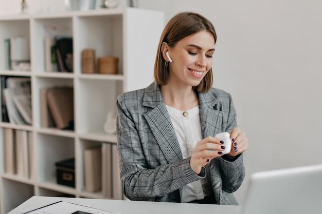 Portret Uśmiechnięta Kobieta W Stroju Biurowym Stawiając Airpods Do Komunikowania Się Z Klientami. Darmowe Zdjęcia
