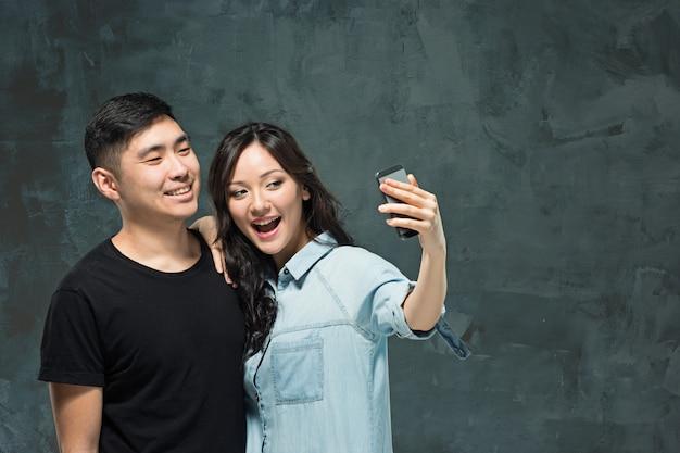 Portret Uśmiechnięta Koreańska Para Na Szarej ścianie Darmowe Zdjęcia