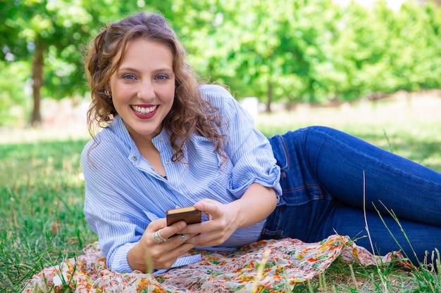Portret uśmiechnięta ładna dziewczyna używa mobilnego internet Darmowe Zdjęcia