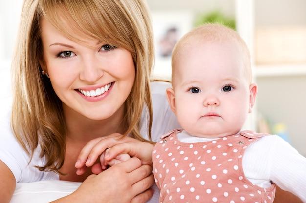 Portret Uśmiechnięta Matka Z Noworodkiem W Domu Darmowe Zdjęcia