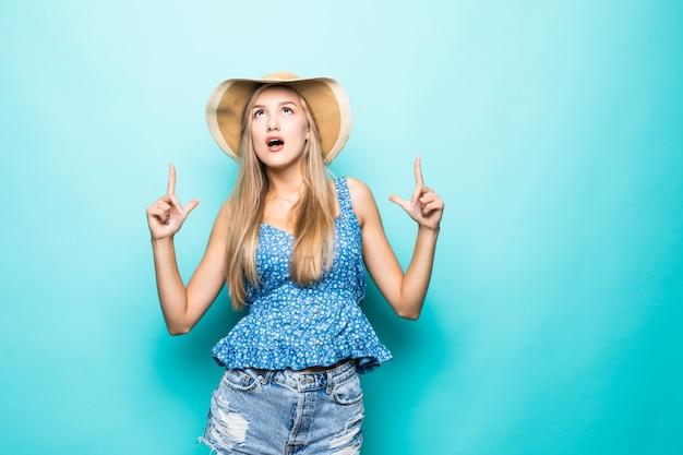 Portret Uśmiechnięta Młoda Kobieta W Letnim Słomkowym Kapeluszu, Pomarańczowe Okulary Wskazujące Palcami Wskazującymi W Górę Na Przestrzeni Kopii Na Białym Tle Na żółtym Tle. Darmowe Zdjęcia