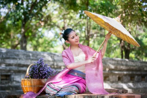 Portret uśmiechnięta młoda kobieta w tajlandzkim lanna tradycyjnym odzieżowym mienie parasolu Premium Zdjęcia
