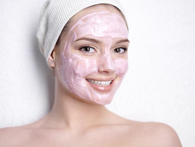 Portret Uśmiechnięta Młoda Piękna Kobieta Z Różową Maską Kosmetyczną Twarzy Darmowe Zdjęcia