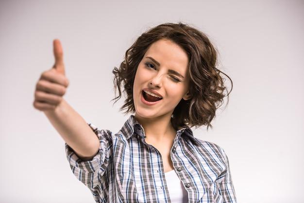Portret uśmiechnięta młoda piękno kobieta pokazuje kciuk up. Premium Zdjęcia