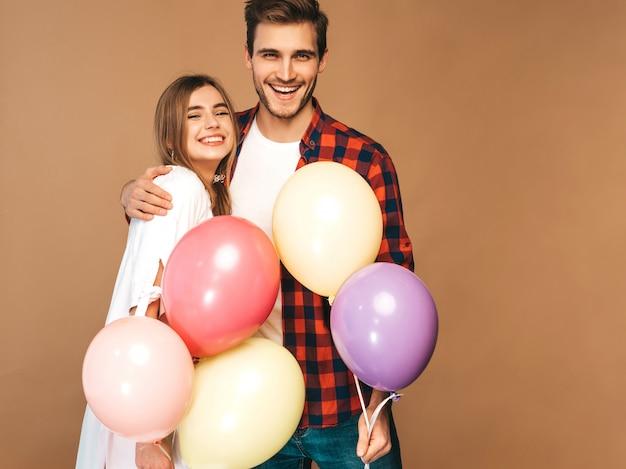 Portret Uśmiechnięta Piękna Dziewczyna I Jej Przystojny Chłopak Trzyma Bukiet Kolorowych Balonów I śmiejąc Się. Szczęśliwa Para Zakochanych. Wszystkiego Najlepszego Darmowe Zdjęcia