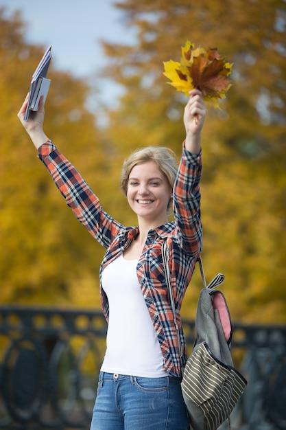 Portret Uśmiechnięta Samica Młodych Studentów Na Zewnątrz Pomieszczeń Gospodarstwa żółtymi Liśćmi Darmowe Zdjęcia