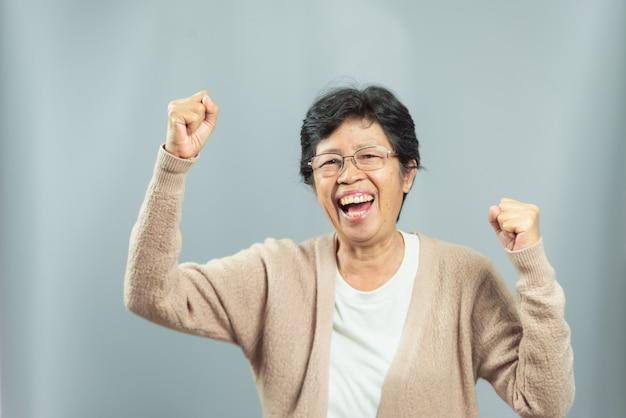 Portret uśmiechnięta stara kobieta na szarość Premium Zdjęcia