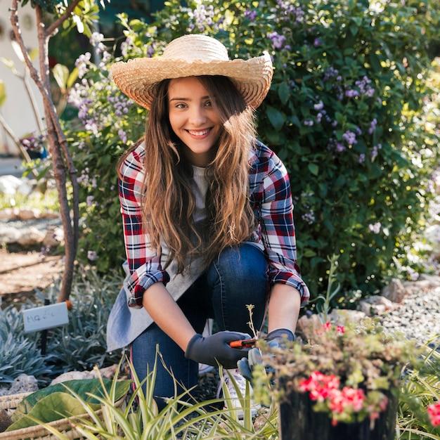 Portret uśmiechnięta żeńska ogrodniczka jest ubranym kapelusz ciie rośliny w ogródzie Darmowe Zdjęcia