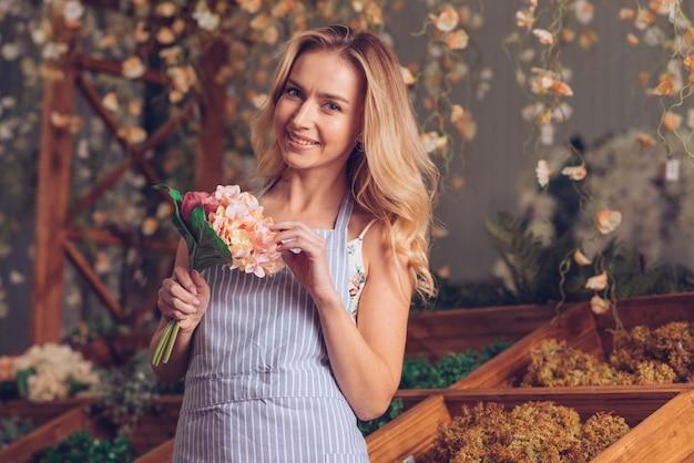 Portret Uśmiechniętej Blondynki Kwiaciarki Mienia Kwiatu żeński Bukiet W Ręce Darmowe Zdjęcia